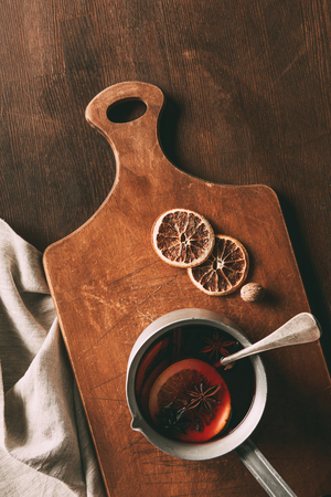 top view of traditional homemade mulled wine with spices on cutting board on wooden table Stock Photo