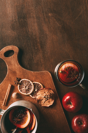 top view of homemade mulled wine with spices and apples on cutting board on wooden background Stock Photo