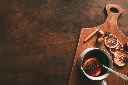 top view of homemade hot mulled wine with spices on cutting board on wooden background