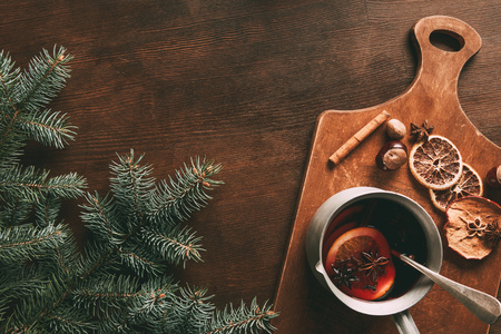 top view of homemade mulled wine with spices on wooden background with pine branch