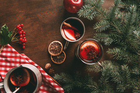 top view of glass cups with homemade hot spiced wine on wooden background with viburnum berries and fir branches
