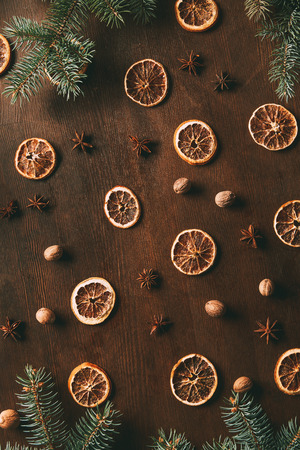 top view of dried orange slices, anise stars and nutmeg seeds on wooden background with fir branches