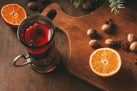 hot mulled wine with spices and orange in glass cup on wooden background Stock Photo