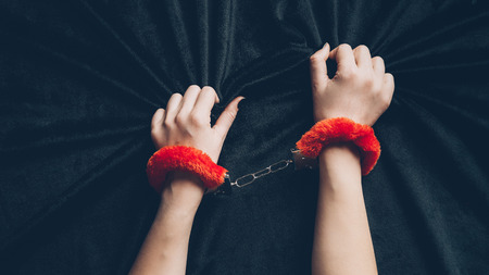 cropped shot of woman in red fluffy handcuffs holding black fabric
