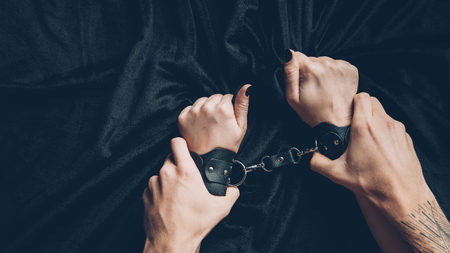 cropped shot of man holding hands of partner in leather handcuffs Archivio Fotografico