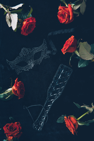 top view of lace mask, leather spanking paddle and beautiful red roses on black