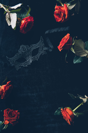top view of lace mask and beautiful red roses on black background