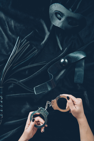 cropped shot of woman holding handcuffs, leather whip, gag and mask on black fabric Stock Photo