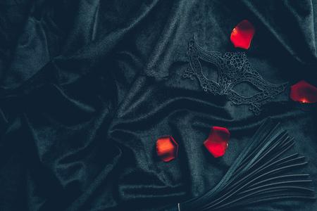 widok z góry skórzanego bicza, płatków róż i koronkowej maski na czarnej tkaninie