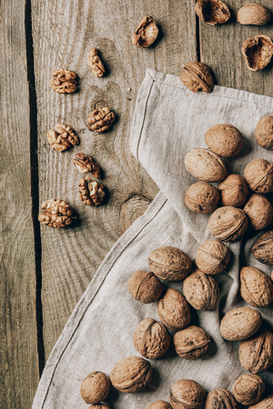 top view of delicious organic walnuts and cloth on wooden table