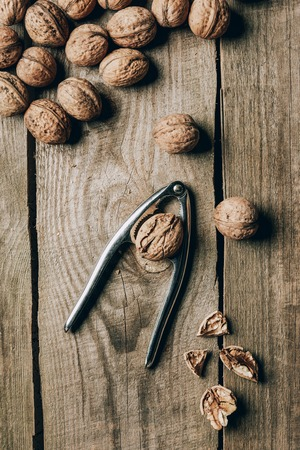top view of tasty healthy walnuts and nutcracker on wooden table Stock Photo