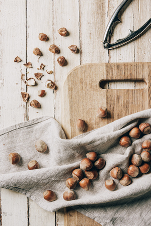 top view of hazelnuts on cloth, chopping board and nutcracker on wooden table Standard-Bild - 110515502