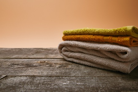close-up shot of stacked colorful towels on rustic wooden table Banco de Imagens