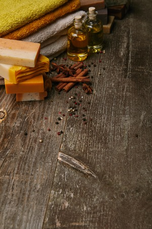 handmade soap pieces with stacked towels, spices and massage oil on rustic wooden tabletop