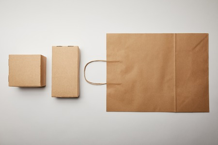 elevated view of arranged view of cardboard boxes and food delivery paper bag on white surface, minimalistic concept