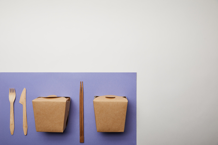 top view of noodle boxes, chopsticks and disposable fork with knife on purple