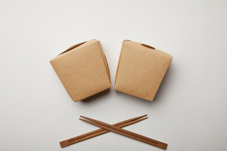 top view of arranged wok boxes and chopsticks on white surface, minimalistic concept Stock Photo