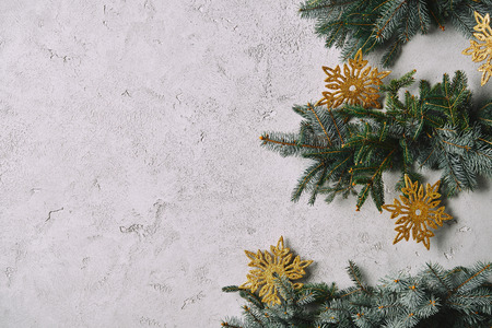 cropped image of handmade Christmas tree with snowflakes hanging on grey wall in room