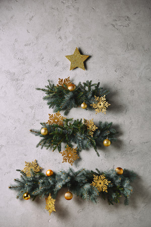 handmade Christmas tree and star hanging on grey wall in room