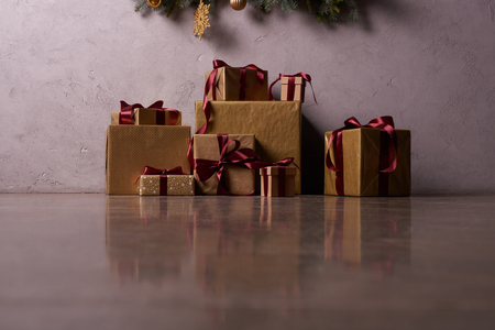 surface level of Christmas gift boxes on floor under christmas tree in room