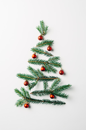 top view of pine branches arranged in christmas tree with toys on white background Zdjęcie Seryjne