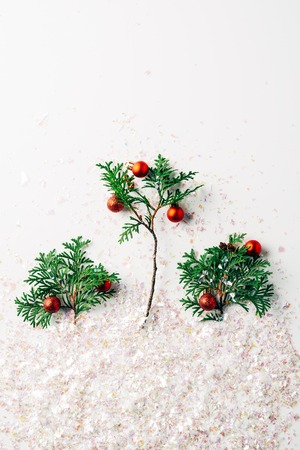 flat lay with pine tree branches decorated with christmas balls with glitters on white surface