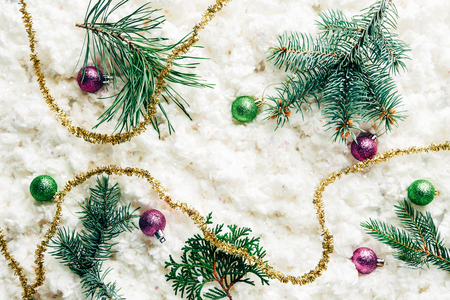 flat lay with pine tree branches, christmas toys and festive garland on white cotton wool background