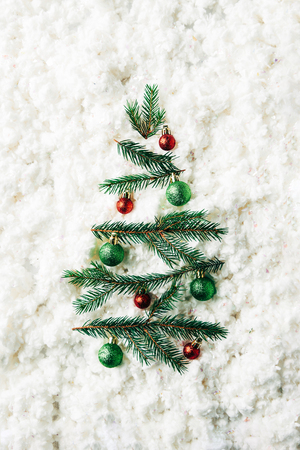 top view of green pine branches with christmas balls arranged in festive christmas tree on white cotton wool backdrop