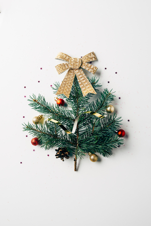 top view of green pine branch decorated as festive christmas tree with bow on white background