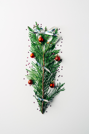 top view of green pine branch decorated as festive christmas tree on white background Stock Photo