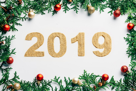 top view of 2019 year sign, pine tree branches and christmas balls on white background 免版税图像