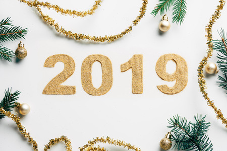 top view of 2019 year sign, pine branches, golden garlands and christmas balls on white background Stock Photo