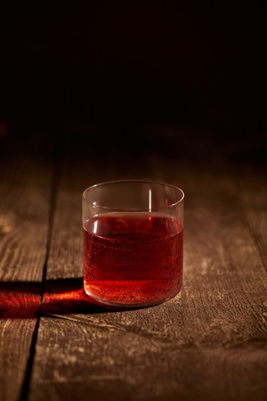 close up view of tasty mulled wine in glass on wooden surface
