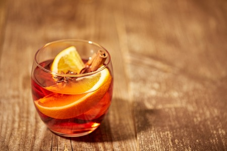 close up view of hot mulled wine drink with orange pieces and anise stars on wooden surface