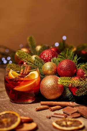 close up view of mulled wine drink in glass and pine tree with christmas toys on wooden surface 写真素材