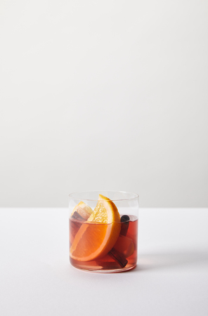 close up view of hot mulled wine in glass with orange pieces on white tabletop on grey background