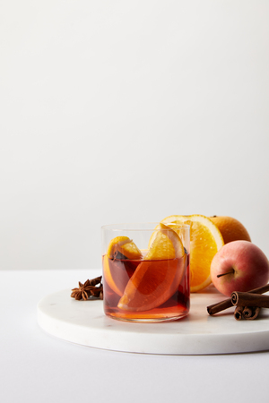 close up view of hot mulled wine in glass, spices, oranges and apple on white surface on grey backdrop