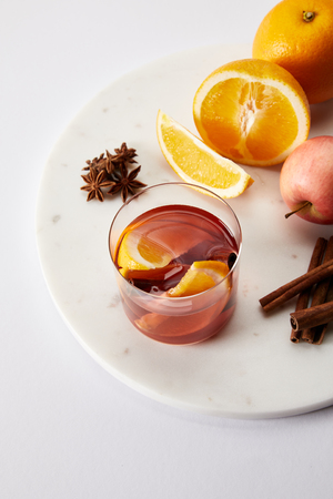 close up view of hot mulled wine in glass, spices and fresh fruits on white surface