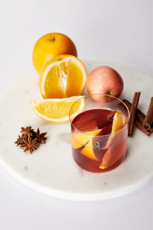 close up view of hot mulled wine in glass, spices, oranges and apple on white tabletop