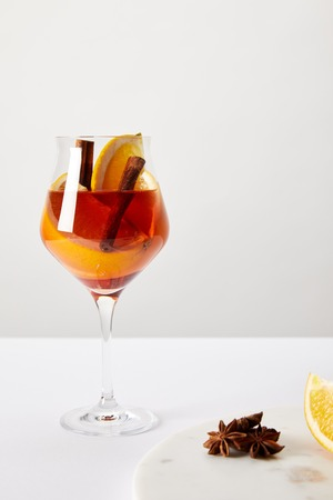close up view of tasty mulled wine with orange pieces and anise stars on white tabletop on grey background