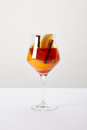 close up view of tasty mulled wine with orange pieces on white tabletop on grey background Stock Photo
