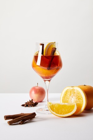 close up view of mulled wine in glass and ingredients arranged around on white tabletop on grey backdrop