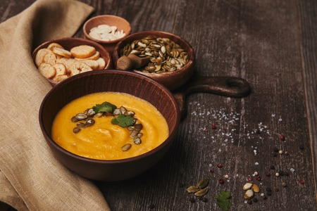 bowl with organic pumpkin soup, sackcloth, pumpkin seeds and rusks on wooden table