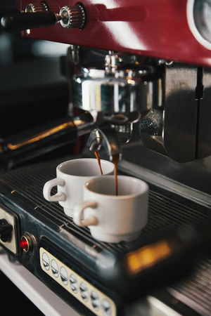 close-up view of coffee machine and two mugs with espresso