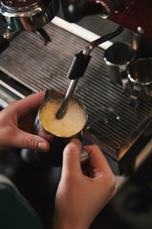 cropped shot of barista preparing cappuccino in coffee machine Stock Photo