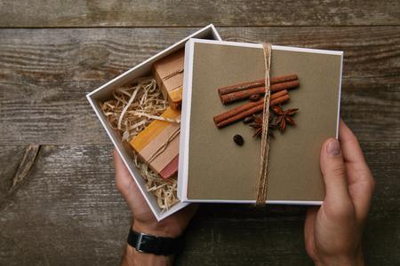 abgeschnittene Aufnahme eines Mannes, der eine Kiste mit handgemachter Seife über einem Holztisch hält?