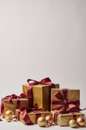 gift boxes with burgundy ribbons and golden christmas balls isolated on white