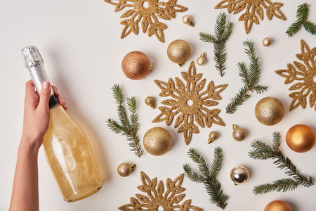 cropped image of woman holding bottle of sparkling champagne near christmas decoration isolated on white