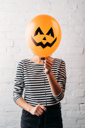 woman holding halloween balloon in front of head 스톡 콘텐츠