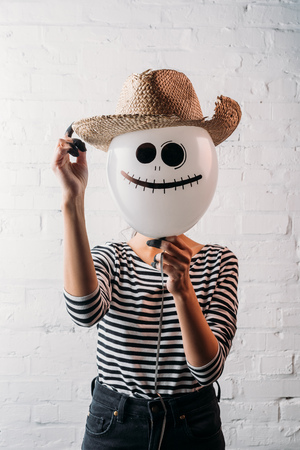 woman holding halloween balloon with straw hat in front of head